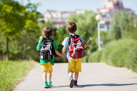 comiendo helado: Dos adorables ni�os en ropa y mochilas de colores, a poca distancia, que sostienen y comiendo helados en una soleada tarde de verano, d�a caliente, ropa casual