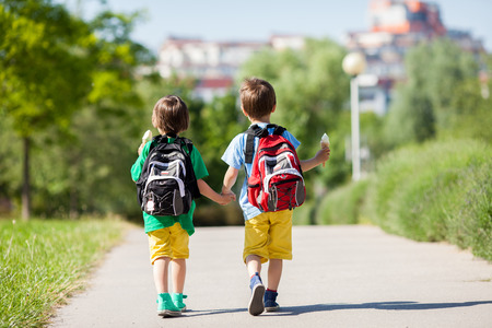 cones: Two adorable boys in colorful clothes and backpacks, walking away, holding and eating ice cream on a sunny summer afternoon, warm day, casual clothing