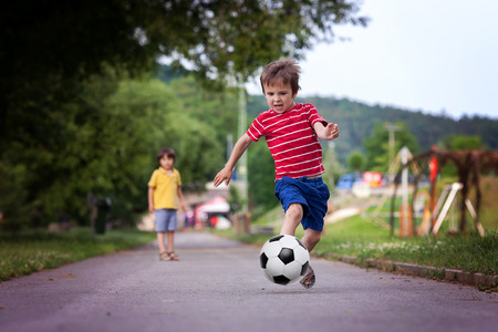 kids activities: Two cute little kids, playing football together, summertime. Children playing soccer outdoor Stock Photo