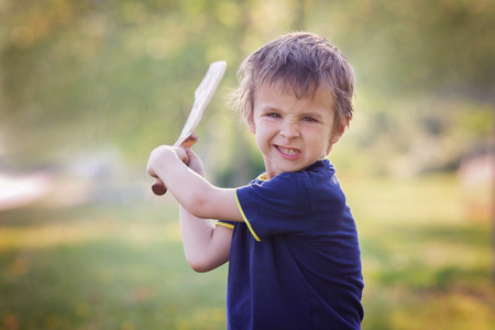 Angry little boy, holding sword, glaring with a mad face at the camera, outdoors in the park Standard-Bild