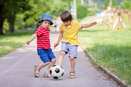 Two cute little kids, playing football together, summertime. Children playing soccer outdoor Stock Photo