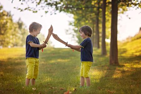 peleando: Dos niños pequeños, sosteniendo espadas, mirando con cara de locos el uno al otro, que luchan al aire libre en el parque