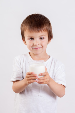 milk mustache: Cute little boy, drinking milk, holding glass of milk, mustaches from the milk, smiling at camera, isolated on white Stock Photo