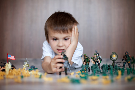 Cute little toddler boy, playing at home with soldiers and figurine toys, playing wars and peace Stock Photo