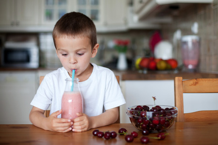 snack: Happy school boy drinking  healthy smoothie as a snack at home, cherries in a bowl on the table Stock Photo