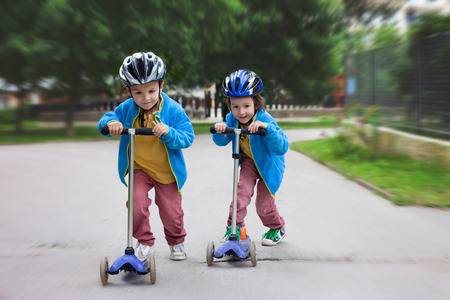 Two cute boys, compete in riding scooters, outdoor in the park, summertime Stock Photo