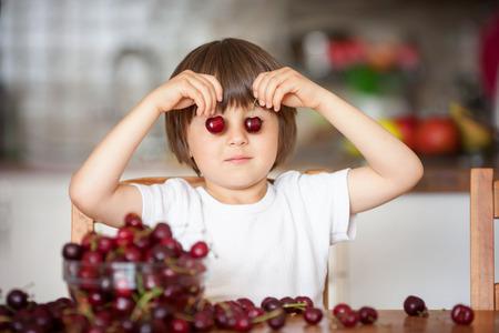 cereza: Niño pequeño lindo, comer cerezas en casa en la cocina, haciendo muecas y jugando con las cerezas, que se divierten Foto de archivo
