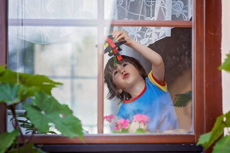 double glass: Sweet little boy, playing with airplane early in the morning on the window, view from outdoor through the window Stock Photo