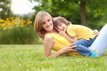 boys and girls: Young beautiful mom and her cute little boy, relaxing and having fun in the park, spring afternoon, yellow clothing Stock Photo