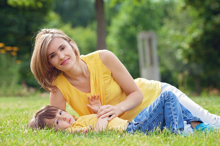 citypark: Young beautiful mom and her cute little boy, relaxing and having fun in the park, spring afternoon, yellow clothing Stock Photo