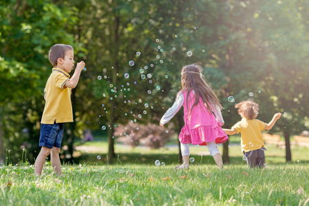 burbujas de jabon: Tres niños en el parque de soplado y persiguiendo las burbujas de jabón y divirtiéndose, día soleado de verano