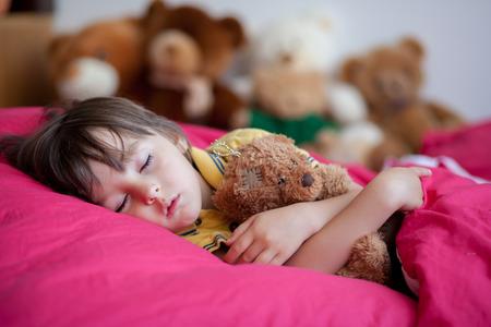 Lieve jongen, slapen in de middag met zijn teddybeer speelgoed