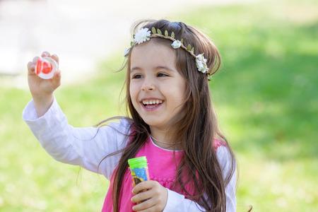Beautiful portrait of sweet lovely little girl blowing soap bubbles in the park, summertime