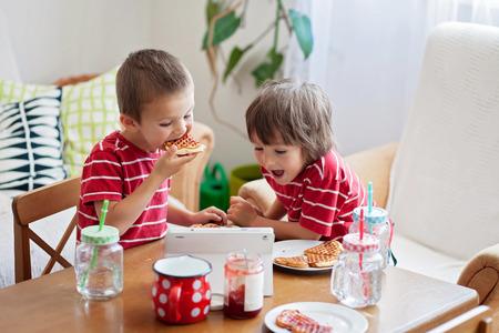 Twee gelukkige kinderen, twee broers, met een gezond ontbijt zitten aan houten tafel in de zonnige keuken, het eten van wafels en kijken cartoon op tablet