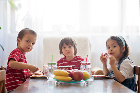 Three happy kids, two brothers and little sister, having healthy breakfast sitting at wooden table in sunny kitchen Standard-Bild