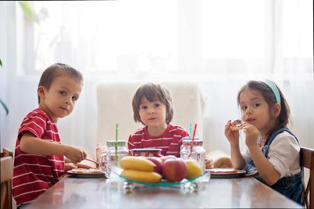 niños desayunando: Tres niños felices, dos hermanos y hermana pequeña, con desayuno saludable sentado en la mesa de madera en la cocina soleado