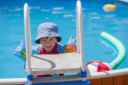 little boy swimming: Sweet little boy, swimming in big swimming pool, summertime