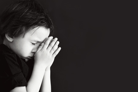 Little boy praying, child praying, isolated black background Stockfoto