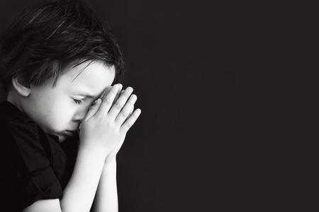 ni�os pensando: Ni�o peque�o orando, orando ni�a, fondo negro aislado Foto de archivo