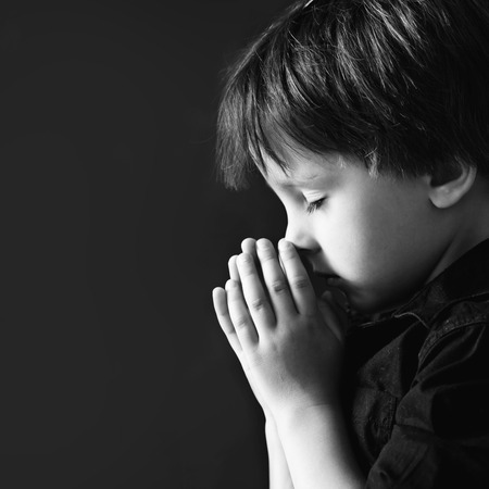 Little boy praying, child praying, isolated black background Stockfoto