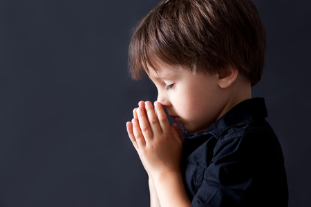 Little boy praying, child praying, isolated black background Stock Photo