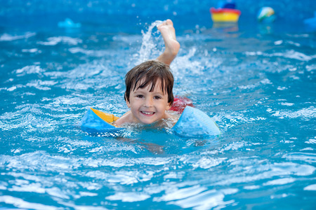 大きなスイミング プール、summrtime で水泳の甘い小さな男の子 写真素材