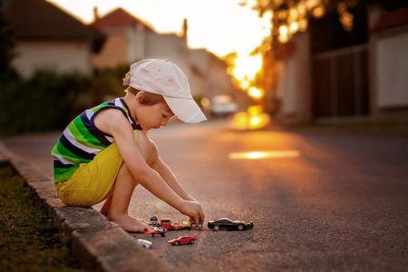juguetes: El niño pequeño lindo, jugando con coches de juguete en la calle en la puesta del sol, el verano, a contraluz