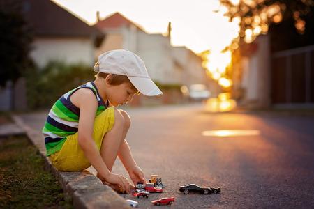 Schattige kleine jongen, spelen met weinig speelgoed auto's op de straat aan zonsondergang, zomer, back-lit Stockfoto
