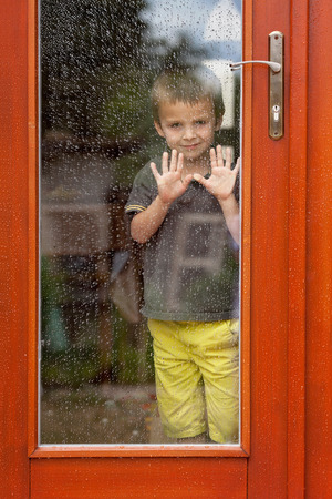 glass house: Little boy behind the window in the rain, looking sad Stock Photo