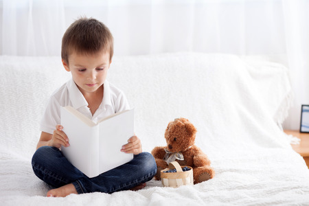 bear berry: Sweet little boy, reading a book in bed and eating blueberries, teddy bear next to him on the bed Stock Photo