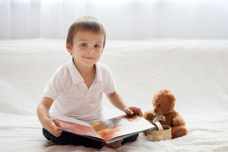boy bedroom: Sweet little boy, reading a book in bed and eating blueberries, teddy bear next to him on the bed Stock Photo