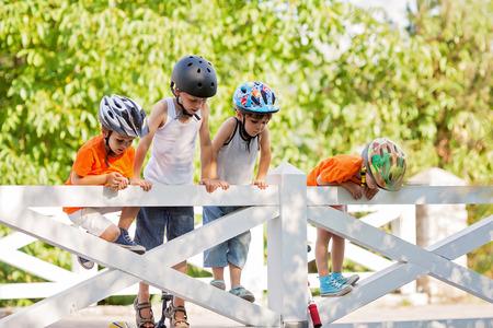 andando en bicicleta: Grupo de ni�os, muchachos, montando en bicicletas y scooters, descansando y jugando en un puente, verano Foto de archivo