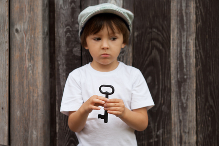 willing: Cute little child, boy, holding big metal key, willing to unlock a door, focus on the key, outdoors