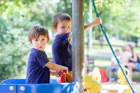 hermanos jugando: Dos ni�os dulces, hermanos, jugando en un barco en el parque infantil, el verano al aire libre