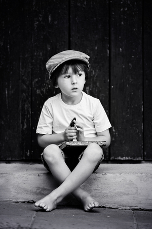 willing: Cute little child, boy, holding big metal key and a book, willing to unlock a door, outdoors