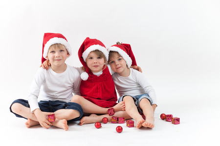 christmas hats: Sweet kids with christmas hats on white background, isolated Stock Photo