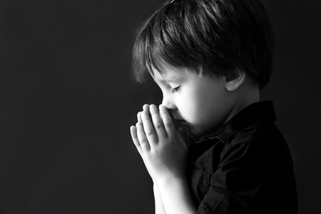 Little boy praying, child praying, isolated black background Banco de Imagens