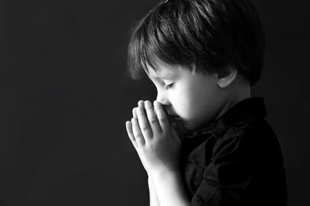 sad child: Little boy praying, child praying, isolated black background Stock Photo