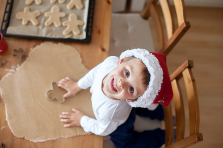 Adorable little boy, preparing cookies for christmas at home, look from above
