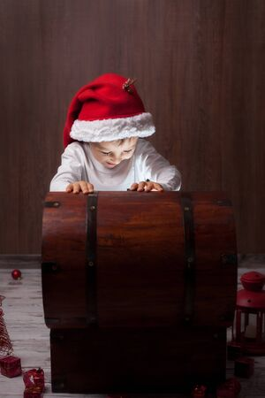 box: Two adorable boys, opening wooden chest, glowing light from inside, happy kids with santa hats