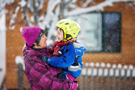 grandma: Young grandmother and her little toddler grandson, playing in the snow, colorful clothing Stock Photo