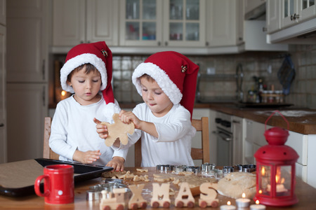baking christmas cookies: Two cute boys with santa hat, preparing cookies in the kitchen at home