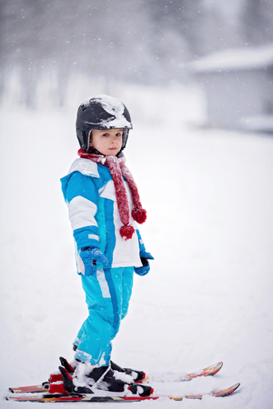 ski goggles: Adorable little boy with blue jacket and a helmet, skiing wintertime Stock Photo