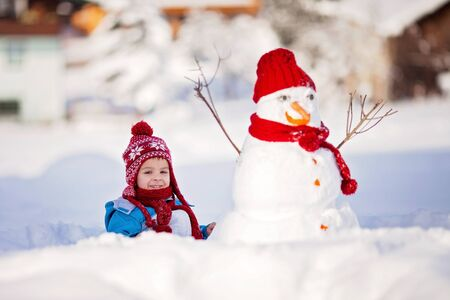 frosty the snowman: Happy beautiful child building snowman in garden, winter time
