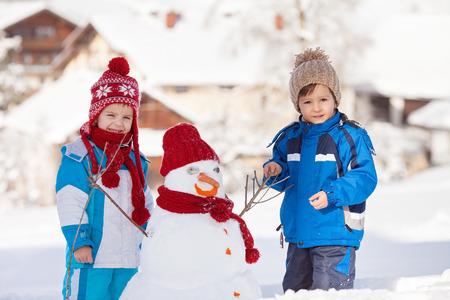 Happy beautiful children, brothers, building snowman in garden, winter time