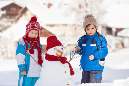 brothers: Happy beautiful children, brothers, building snowman in garden, winter time