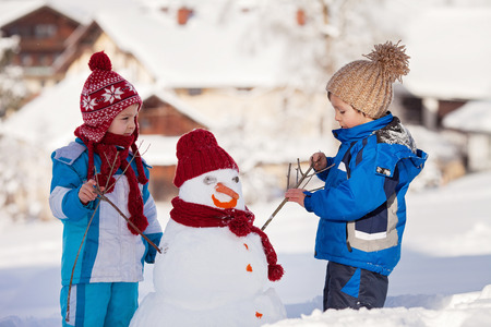 frosty the snowman: Happy beautiful children, brothers, building snowman in garden, winter time