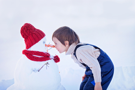 Happy beautiful child building snowman in garden, winter time, nose to nose with the snowman Standard-Bild