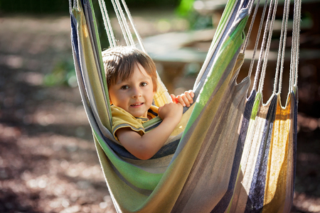 entertaining: Cute little boy laughing in hammock, child entertaining