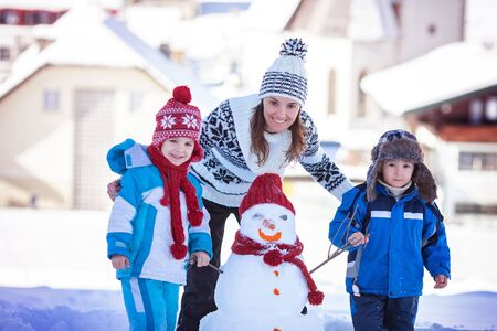 frosty the snowman: Happy beautiful family building snowman in garden, winter time, mom and two kids